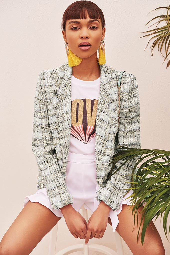 A white tee with a logo, paired with white shorts and a blazer in a minty color looks so chic. The model also wears a pair of long yellow tassel earrings to add on that summer vibe. Image by River Island.