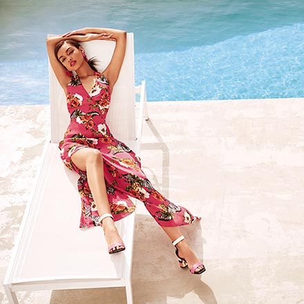 A beautiful maxi dress with a floral print like this, worn by a woman lying on a sunbed by a pool, can be worn from morning till dusk. Image by River Island.