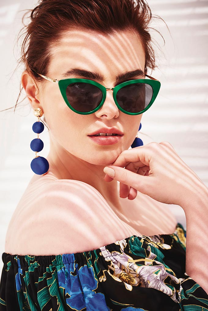 These green cat's eyes sunglasses paired with a up-hair-do and long blue statement earrings look so posh on this brunette woman. Image by River Island.