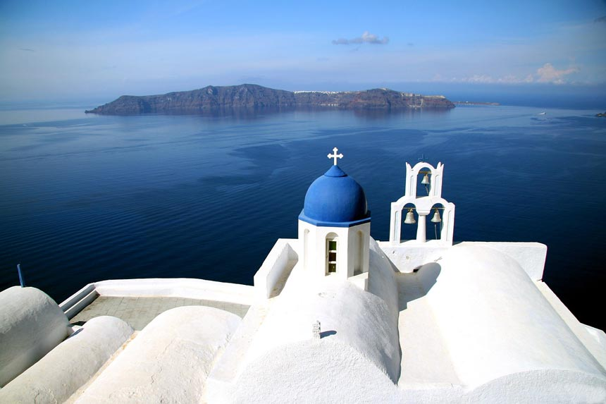 The Aegean Sea as seen from the roofs of a white church in Santorini.
