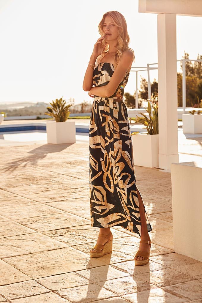 A maxi print dress in black and gold tones inspired by the tropics looks fab on this blonde model who has paired it with beige wedge shoes. Image by Sosandar.