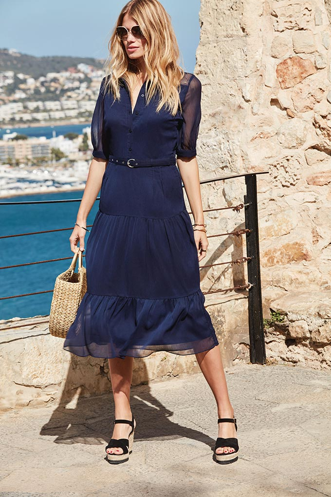 What a gorgeous midi navy blue dress. So simple and chic, paired with a straw bag and wedge platforms. This blonde surely looks good in it. Image by Sosandar.