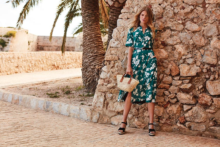 Another gorgeous green dress with a white floral print worn by a model paired with a cute small straw bag and wedge platform shoes. Image by Sosandar.