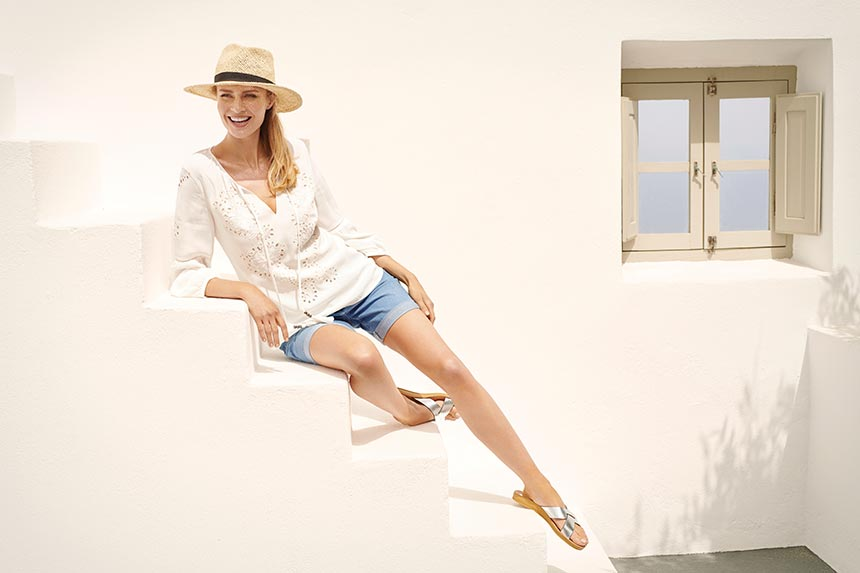A boho style white shirt over denim shorts with flat sliders and a straw hat looks perfect at a Greek island or any other resort for that matter. This model looks laid back as she sits on the stairs in front of a Greek home facade. Image by Wallis.