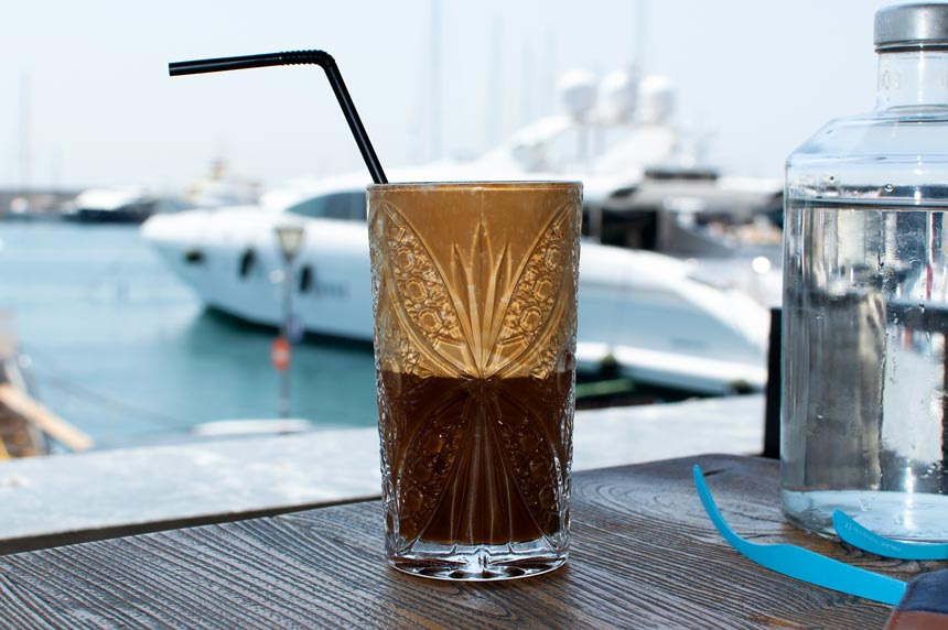 A frappe coffee served in a glass with a sea view in the background. Image by Antonis Drakakis. Copyright Te Esse.