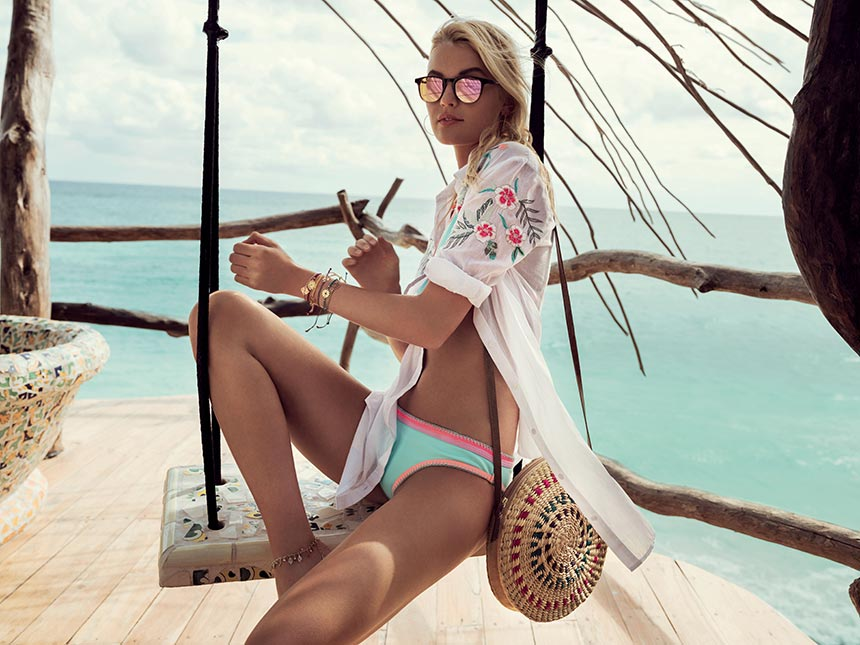 Just love her beach outfit. Blonde woman on a swing with a turquoise sea in the background, wearing a shirt dress, a straw bag, mirror sunshades and lots of bracelets on her wrist. Image by Accessorize.