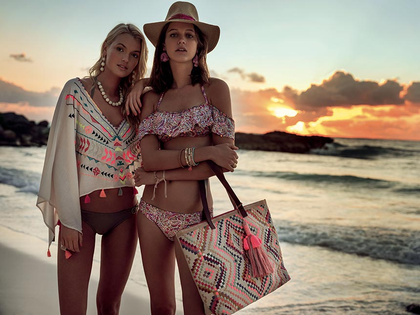 Wow! Two beautiful women dressed in swimsuits with lots of accessories and a gorgeous sunset in the background. Image by Accessorize.