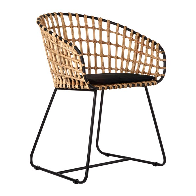 A curvy rattan chair with a black seat cushion. Image by Amara.