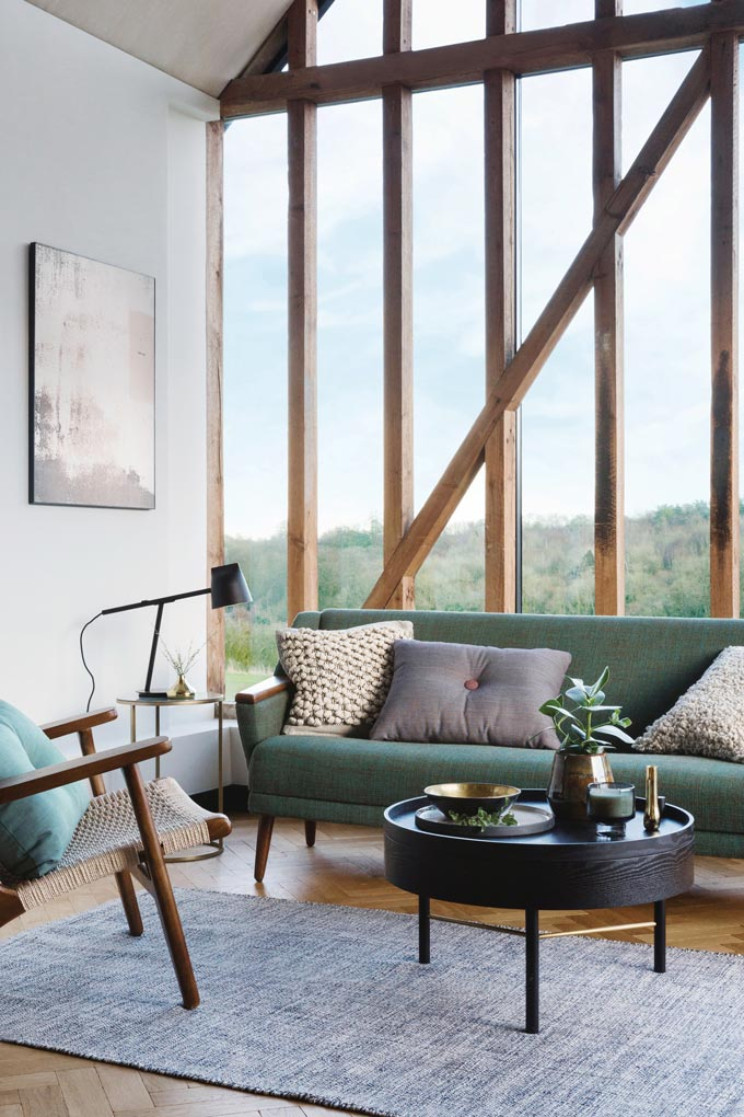 A very elegant sitting room with green sofa in front of a large window opening. Notice that both the sofa and armchair are wooden, one of the 2018 sofa trends. Image by Amara.