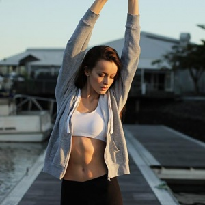 A girl in a sports outfit with her arms raised where her flat tummy shows.