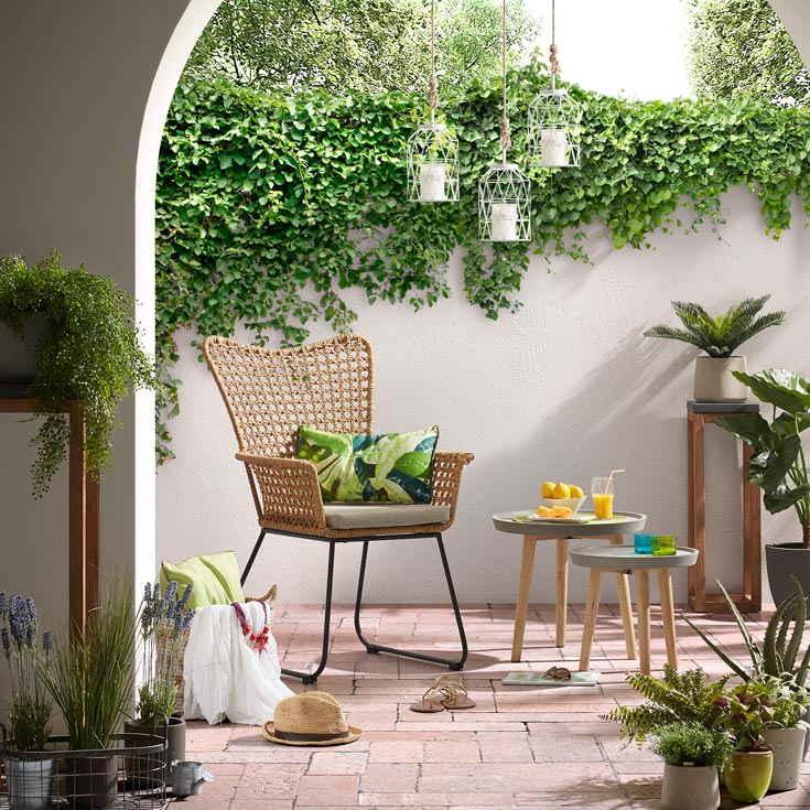 A rattan chair in a patio with lots of greenery around, looking casually stylish. Image by Cuckooland.