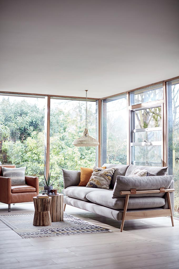 A beautifully styled space with large window openings and lots of natural light with a wooden sofa and a leather armchair create a cozy Scandiboho vibe. Image by DFS Furniture.