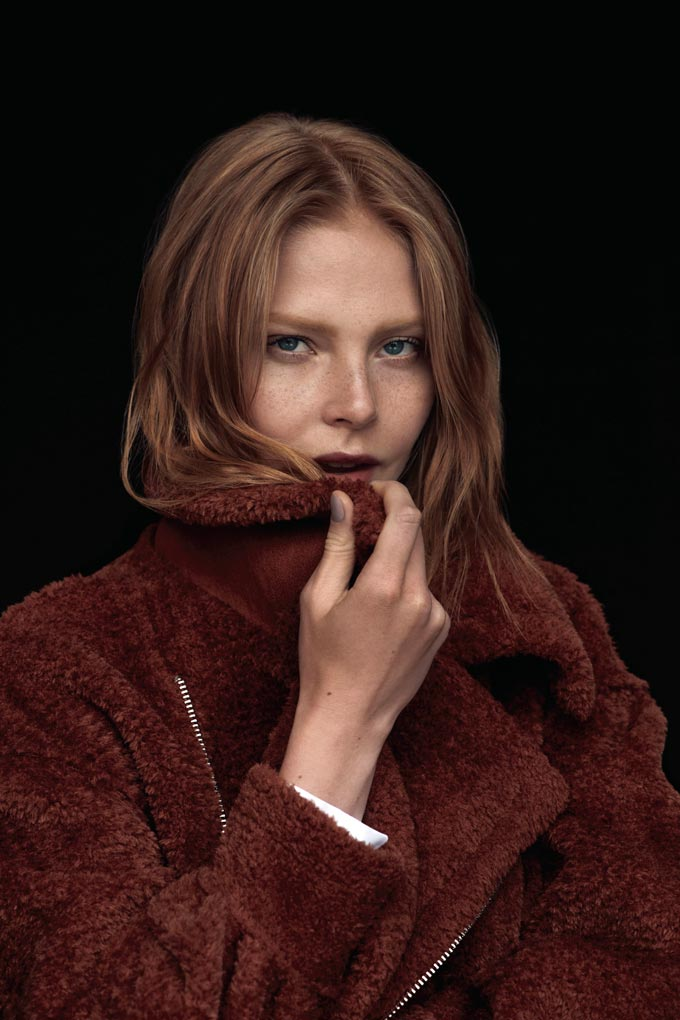 Close up of a beautiful woman dressed in a rusty colored coat. Image by Dorothy Perkins.