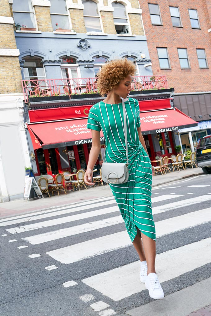 Love this green! Perfect on this dress worn by a young woman paired with a light grey crossbody bag and white sneakers while walking in the city. Image by Dorothy Perkins.