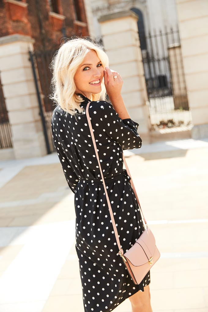 Polka dots are always a good idea. A black polka dot dress paired with a pink handbag worn by a blonde woman in the city. Image by Dorothy Perkins.