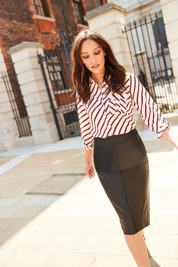 I just love leather skirts in the fall. A brunette woman wearing a shirt with a geometrical print paired with a leather knee length skirt. Image by Dorothy Perkins.
