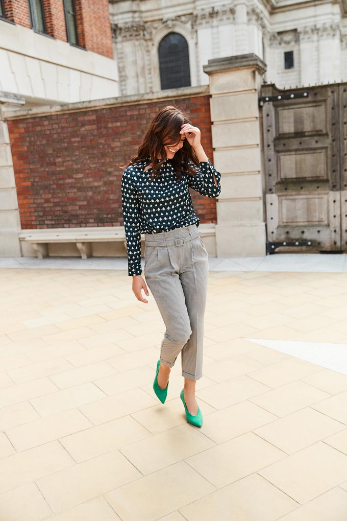 Grey hight waisted pants paired with a black print shirt and emerald green high pumps, worn by a young woman in a town. Image by Dorothy Perkins.