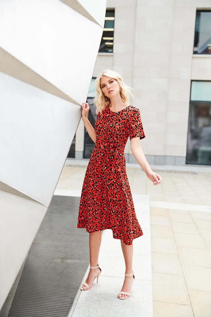 A lovely rusty colored dress with animal print worn by a young blonde woman in high sandals. Image by Dorothy Perkins.