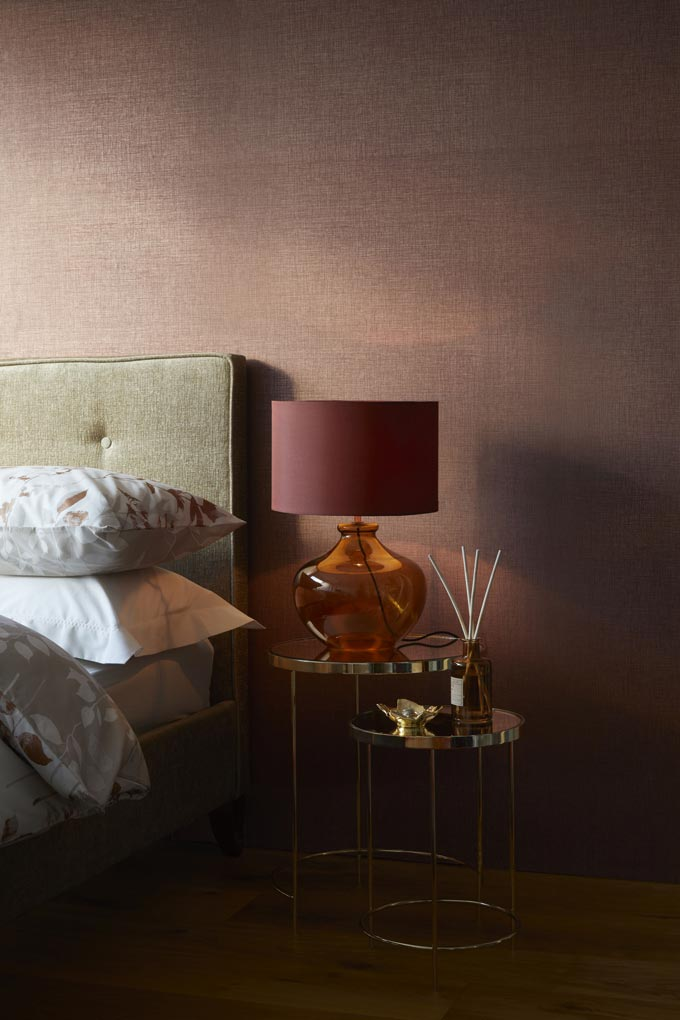 Partial view of a bedroom with a dark rusty accent wall. Love the rusty hue lampshade of the table lamp on the side table. Image by Dunelm.