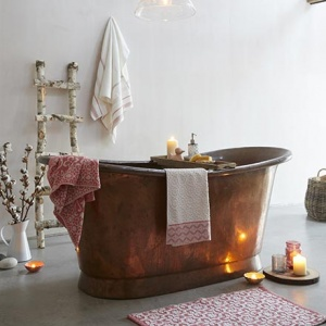 A soothing ambiance in a bathroom like this is dreamy. A copper free standing tub, soft towels and lit candles - is all you need. Image by Dunelm.
