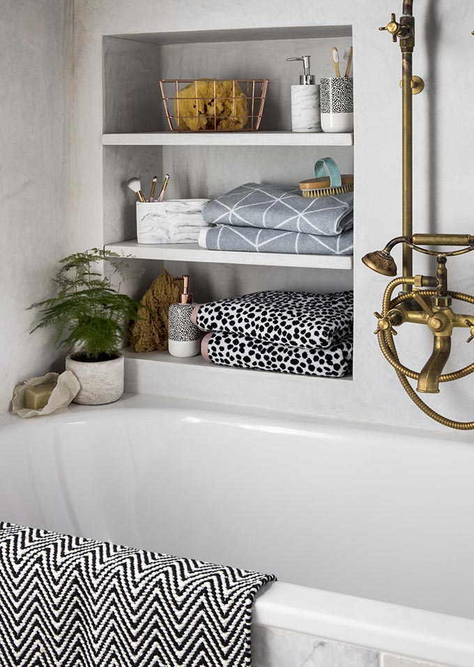 I just love shelves in wall inserts with towels and decor next to a bathtub. So cozy! Image by George Home.