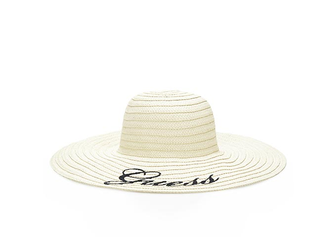 A white straw hat with its logo Guess on it. Image by GUESS.