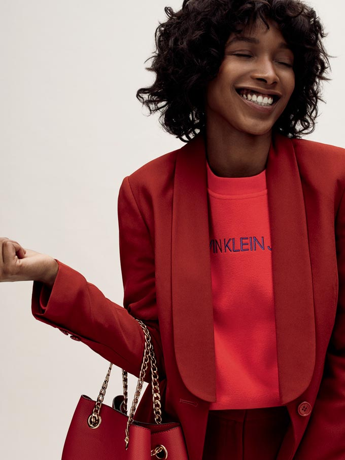 Muted red, one of the trending fall colors, seen here on a coat, a logo tee and a handbag worn by a young black woman. Image by House of Fraser.