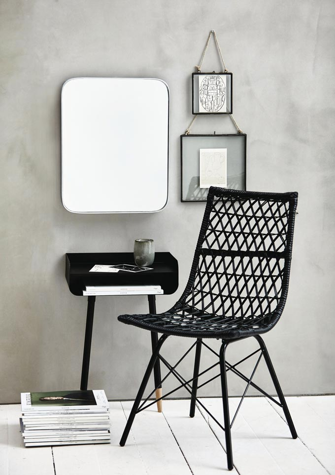 A Lene Bjerre Netta Dining Chair in black rattan in front of a black contemporary vignette. Image by Houseology.