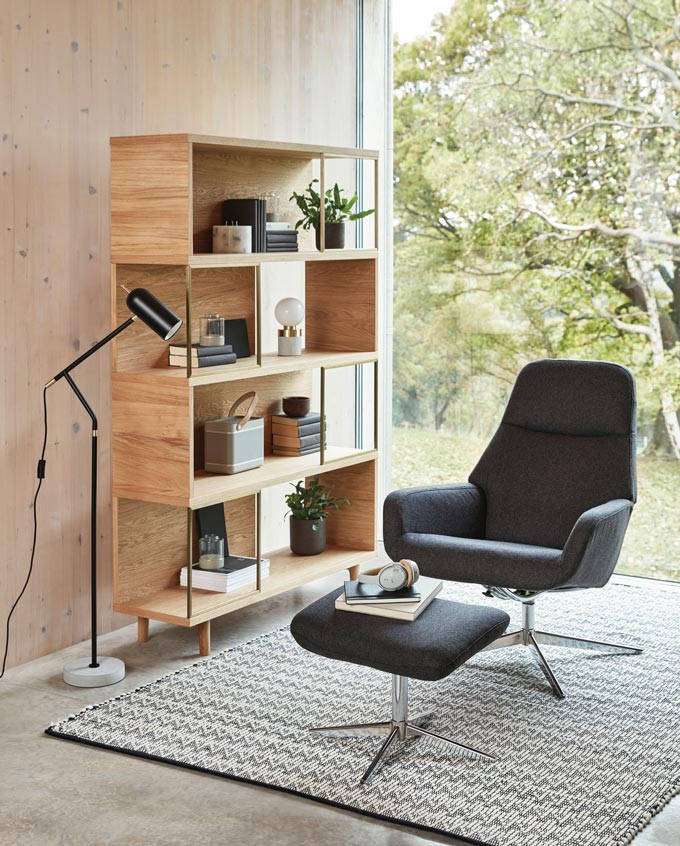 A contemporary reading vignette with a Japandi flair. The wooden bookcase is darker than the accent wooden wall. It is decorated with black spine books and small plants. No frills. The black armchair and stool add a black contrast to balance everything out. Image by John Lewis.