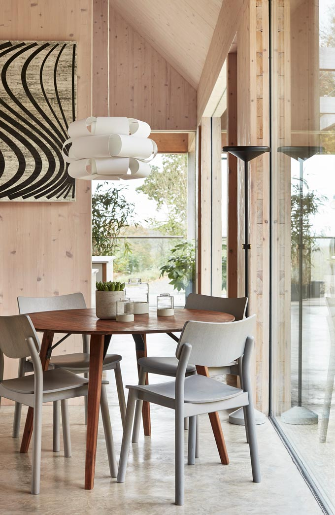 A Japandi styled dining space with a whimsical pendant light over the round dark stained wood dining table. The surrounding walls are made of light colored wood. Large windows allow for lots of natural light. Image by John Lewis.