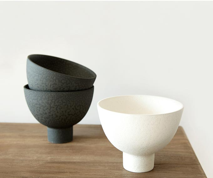 A stack of black Japanese styled bowls on the left and a cream white bowl on the right. Image by Kelly Hoppen.
