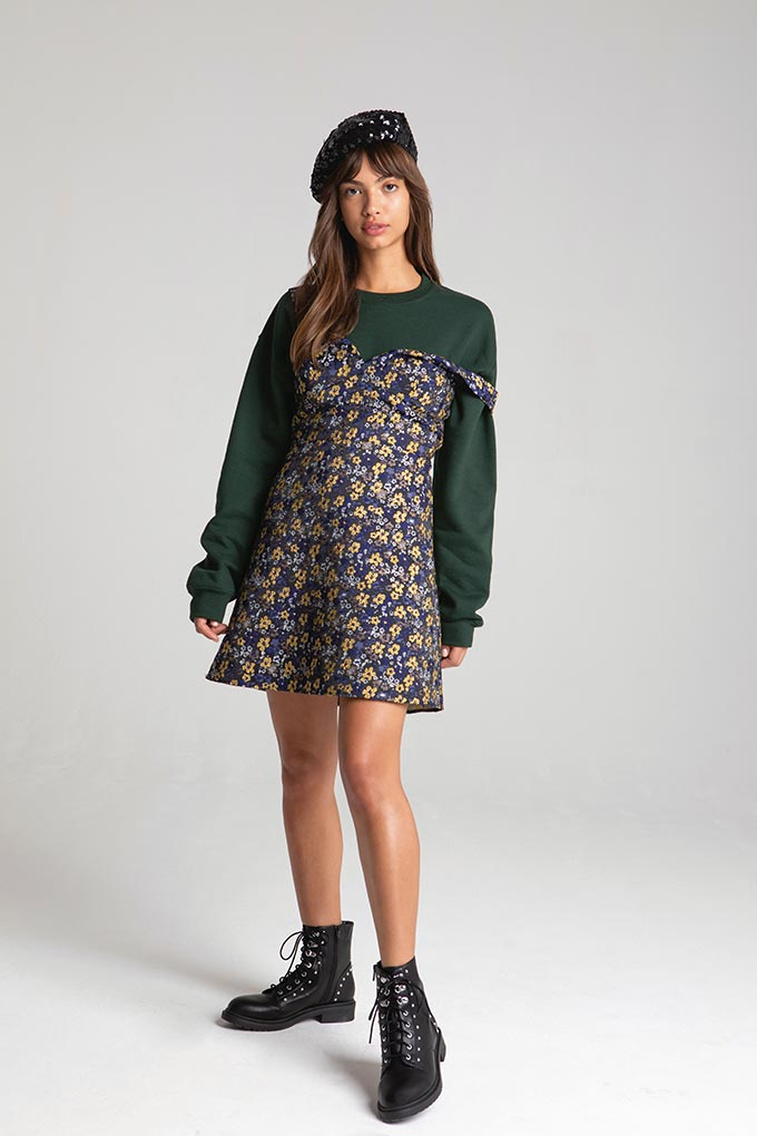 A mini dress over a dark green shirt is a great stylish statement. This young brunette is wearing them with black strappy books and a beret hat for a cool fall style. Image by Miss Selfridge.