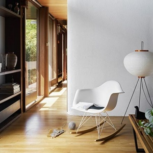 The Vitra RAR Eames plastic rocking armchair paired next to an Akari floor lamp in a house vignette with lots of wooden shelving and a wooden floor. Image by Nest.co.uk.