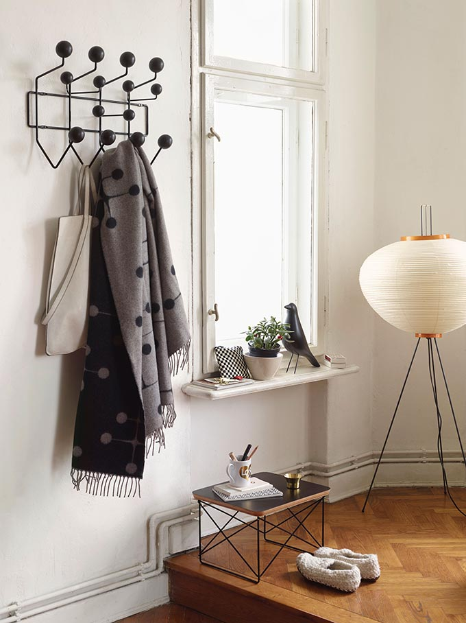 A entryway vignette with a coat hanger on the wall, and an Akari floor lamp by the window. Image by Nest.co.uk.