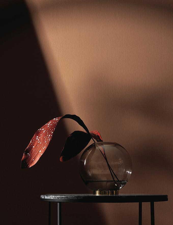 A glass vase with a brass base sitting on a side table with a leafy foliage in a red rusty hue. The saturated rusty hue of the background wall makes a serious design statement. Image by Nest.co.uk.