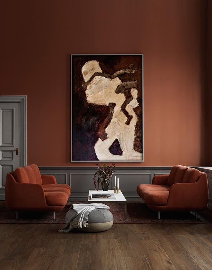 A very sophisticated sitting space with rusty colored sofas with a white coffee table in between them, against a rusty color wall with a large accent artwork. Image by Nest.co.uk.