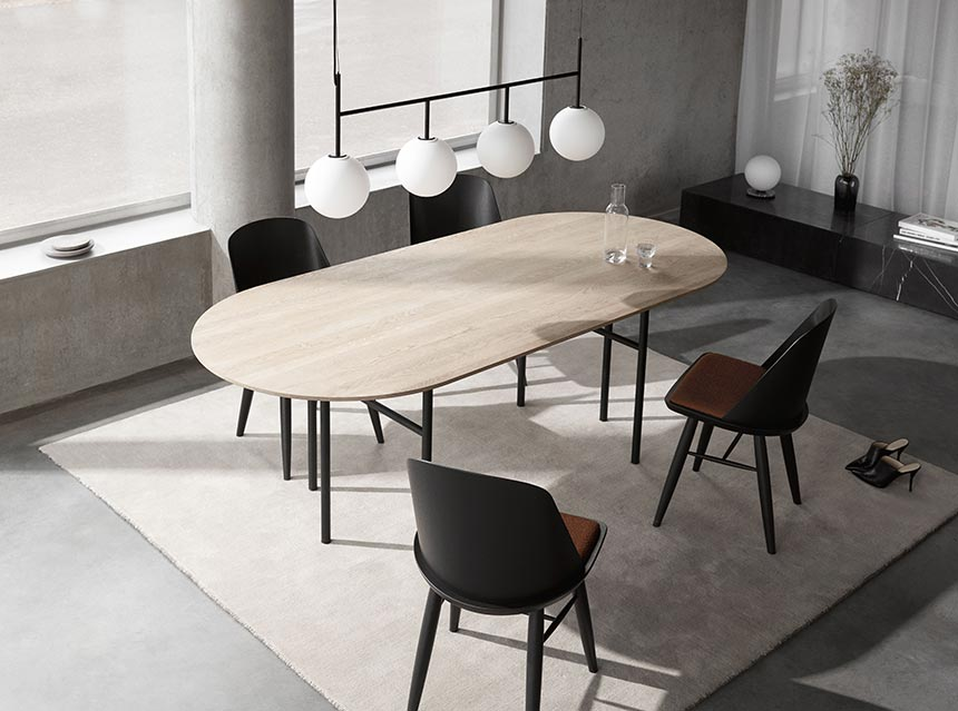 A contemporary dining setting with a natural light wooden table top in contrast to the black frame chairs and rusty color seating with a pendant light composed of four white glazed globes, creates the perfect balanced Zen space. Lots of contrast, airy lines, curves and easy flows. Image by Nest.co.uk.