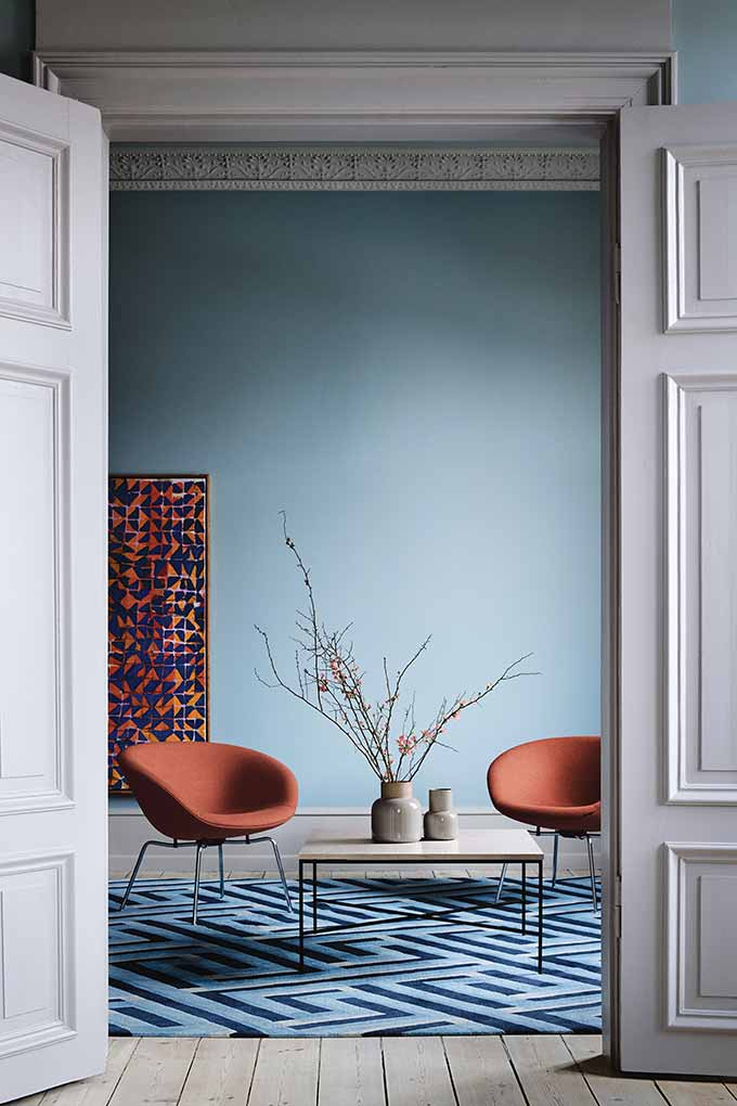 Two gorgeous Fritz Hansen Pot chairs with a white coffee table in between them on top of a blue area rug and a blue wall room. Image by Nest.co.uk.