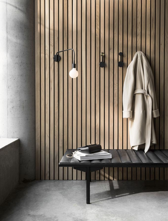 Japandi style. A black contemporary bench against an accent wall made of wooden planks and a coat hanging hooks. Image by Nest.co.uk.
