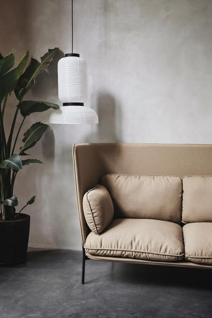A pastel beige sofa with a plant besides and a rice paper lantern atop giving that Japandi flair to this vignette. Image by Nest.co.uk.
