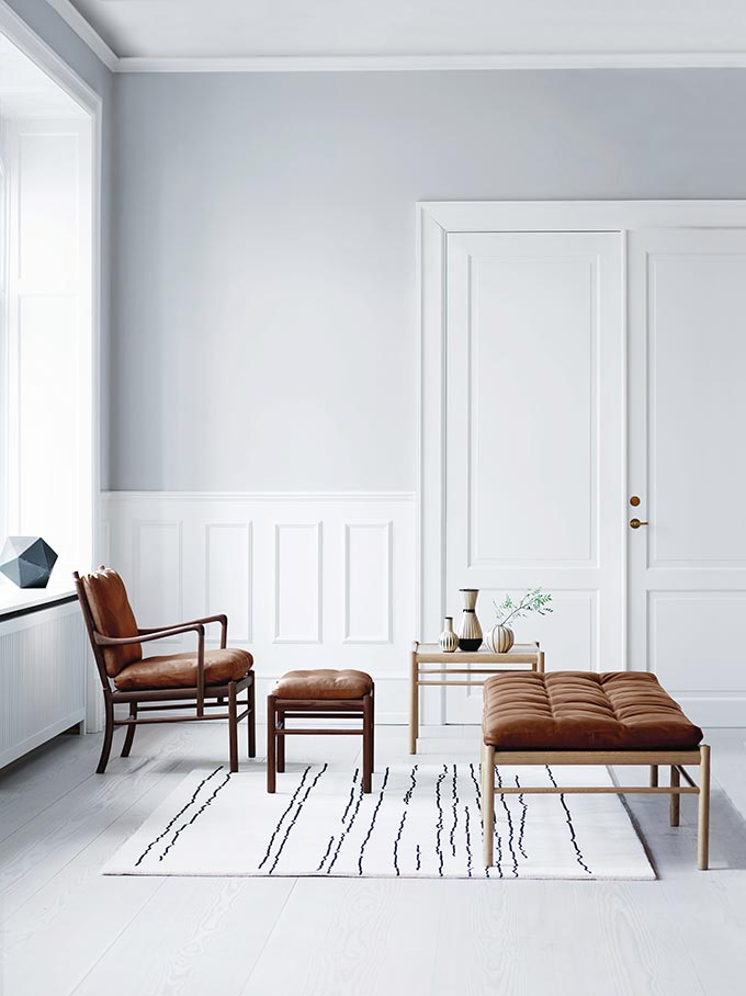 A white Scandi styled sitting room with a wooden armchair and tanned upholstery paired with a wooden daybed. Image by Nest.co.uk.