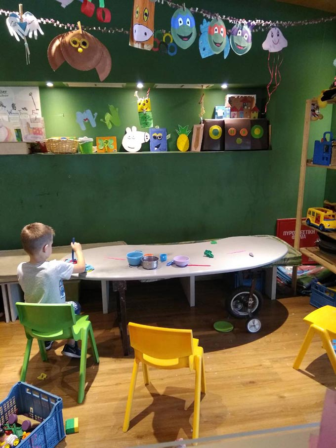 A boy sitting in a green child chair in a Montessori styled play-station. Image by Elisabeth.