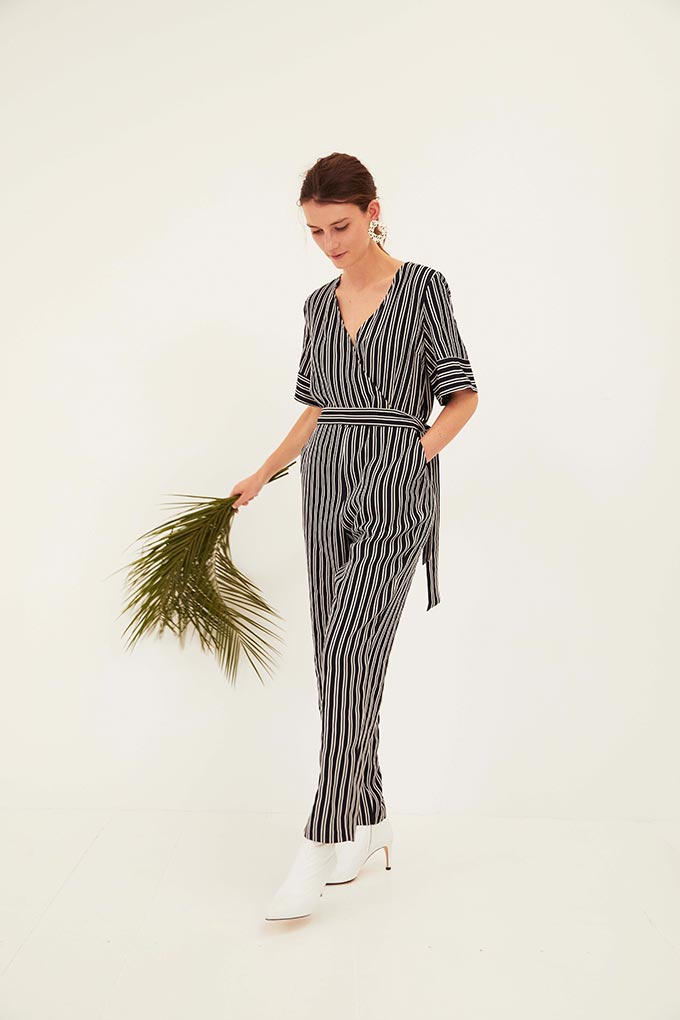 A stylish woman in a striped jumpsuit paired with white boots. Image by Oliver Bonas.