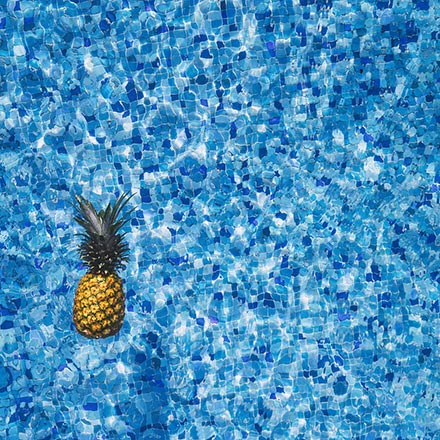 A pineapple floating on a pool.