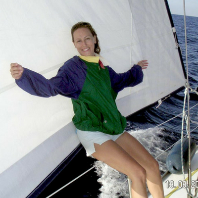 Velvet leaning against an open sail while at cruising with a sailing boat.