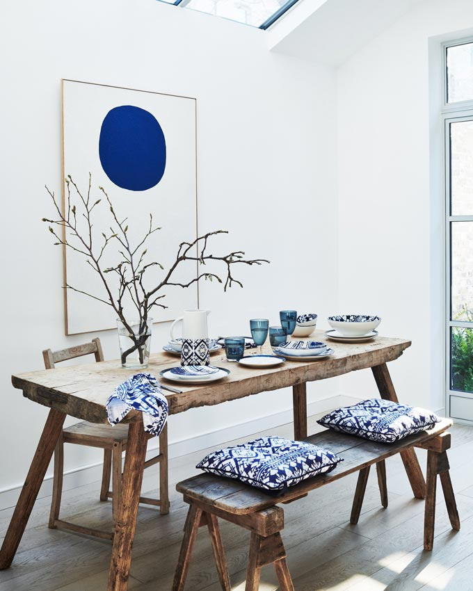 Shibori patterns on textiles and dinnerware styled on a rustic dining setup with a large artwork (a big blue circle on a white canvas). Image by SainsburysHome.