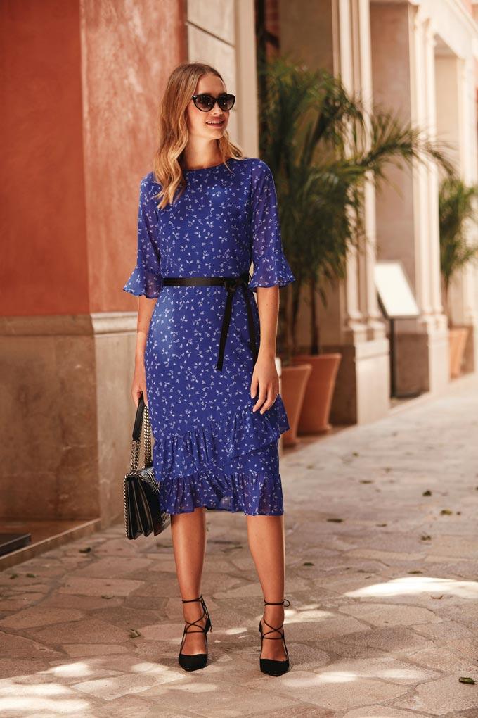 A beautiful royal blue dress with a small print, worn by a beautiful woman in black high heels and black handbag. Image by Sosandar.