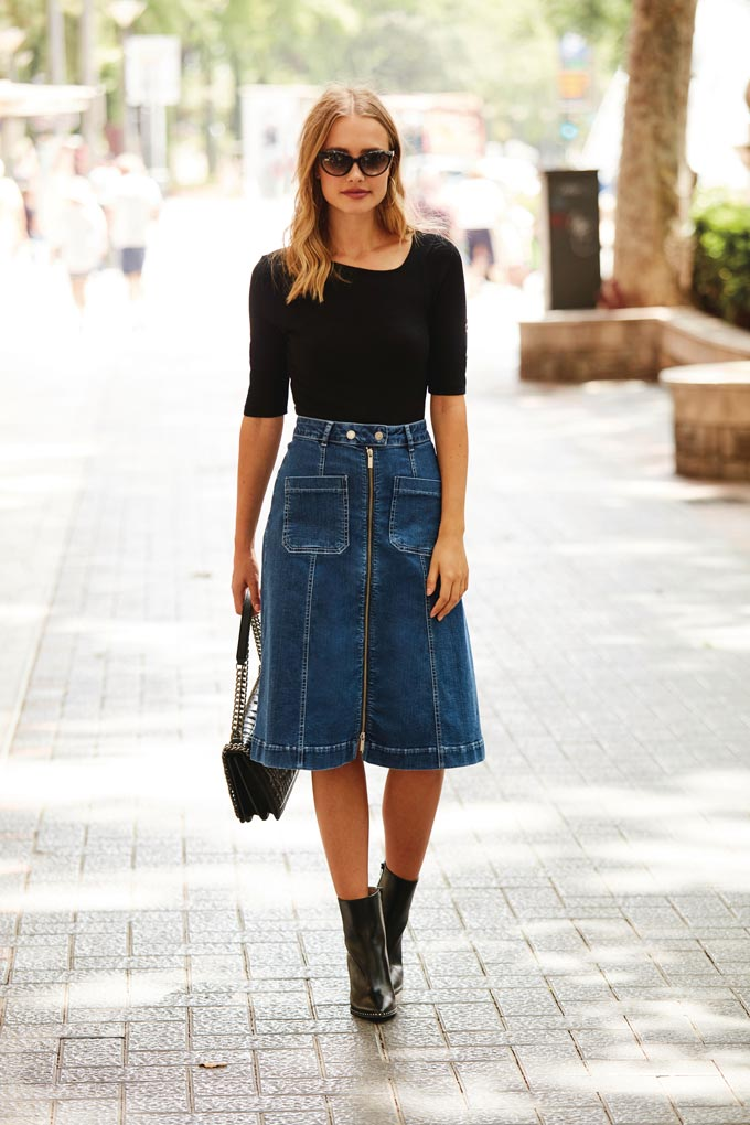 I love a black top with an A line jean skirt, a pair of black ankle boots and a black bag as worn by a pretty blonde woman walking down the street. Image by Sosandar.