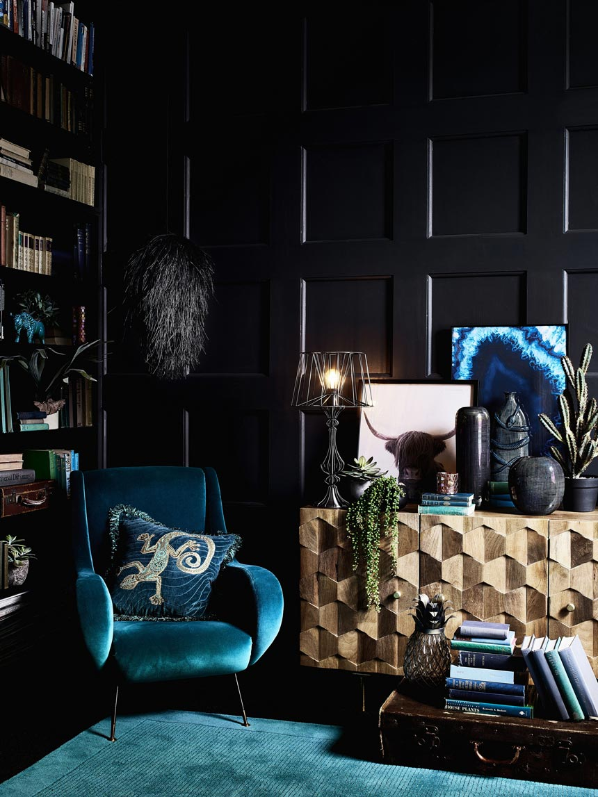 Maximalism. A dark blue moody corner with a built in bookcase, a plush velvet armchair, a color coordinating area rug and a sideboard with a geometric pattern for even more texture. Image by Debenhams.