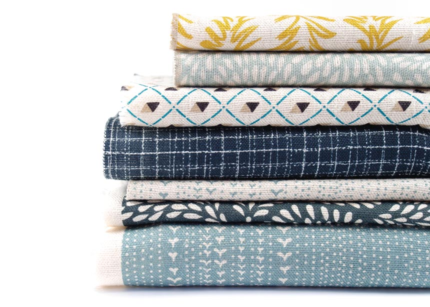 A stack of various linen textiles in various colors and patterns. Image by Allthefruits.